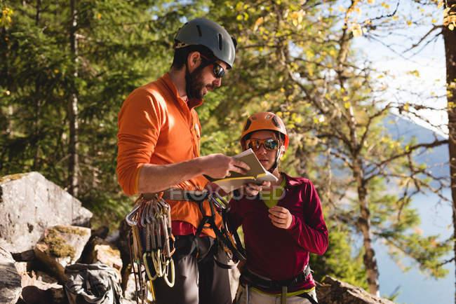 Пара туристов смотрит на карту вблизи горы — стоковое фото