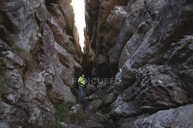 Hiker looking up while standing st the cave entrance with backpack — Stock Photo