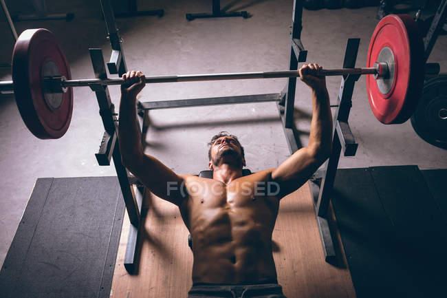 Накладные расходы на упражнения мускулистого человека с штангой в фитнес-студии — стоковое фото