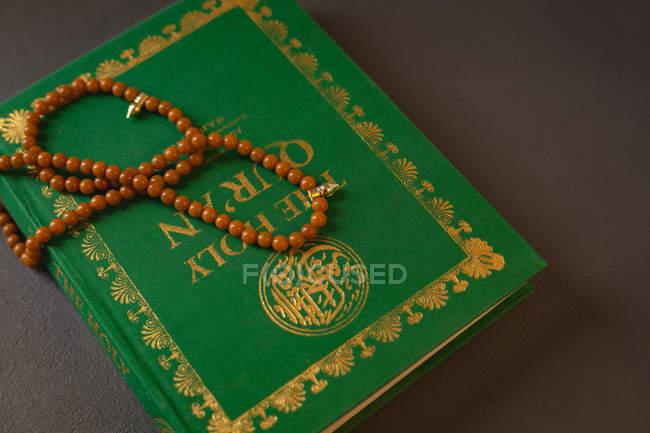 Close-up de grânulos de oração mantidos no Alcorão Sagrado — Fotografia de Stock