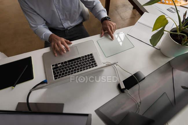 Geschäftsmann nutzt digitales Tablet aus Glas bei der Arbeit am Laptop im Büro. — Stockfoto