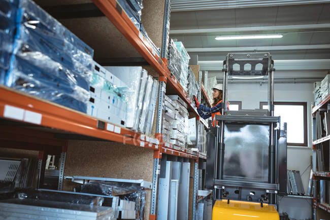Arbeiterin fährt Gabelstapler in Lagerhalle — Stockfoto