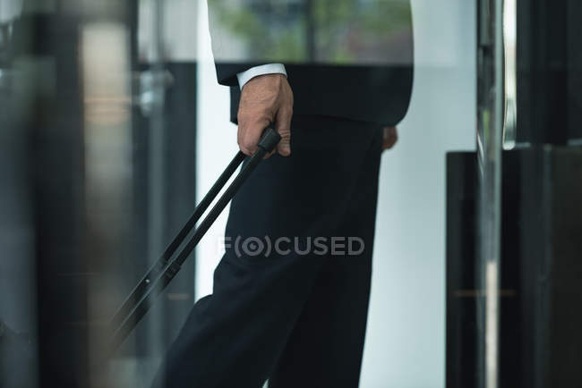 Cropped image of businessman with trolley bag leaving hotel — Stock Photo