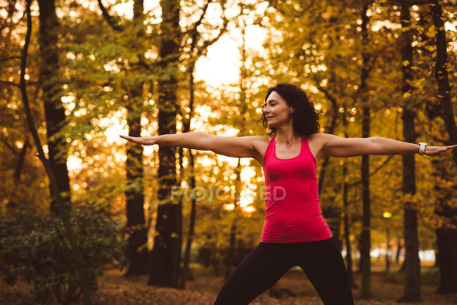 Woman performing exercise in forest on a sunny day — Stock Photo