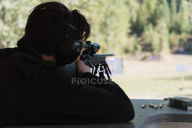 Un homme vise un fusil de sniper sur une cible dans un champ de tir par une journée ensoleillée — Photo de stock