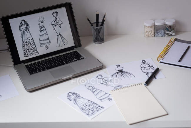 Sketches of design on table and laptop screen in design studio. — Stock Photo