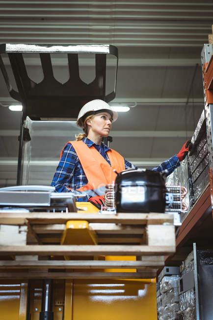 Trabajadora comprobando parte de la máquina en fábrica - foto de stock