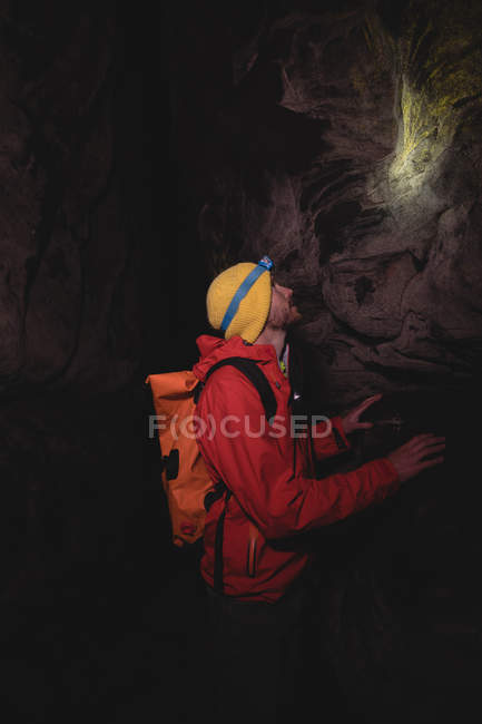 Hiker wearing head torch, inspecting rocks in a dark cave — Stock Photo