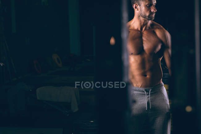 Thoughtful man standing in in fitness studio — Stock Photo