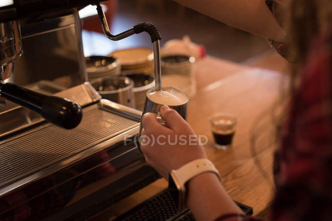 Woman preparing coffee at counter in cafe — Stock Photo