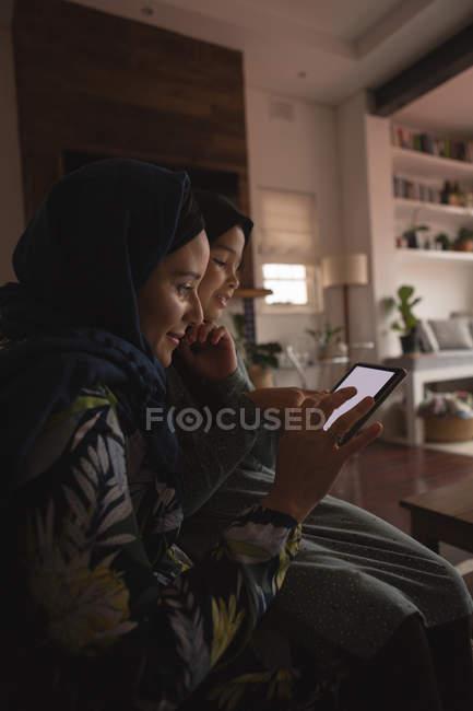 Мусульманская мать и дочь используют цифровой планшет дома — стоковое фото