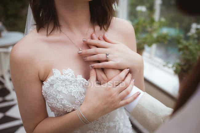 Gros plan du marié plaçant sa main sur la poitrine des mariées — Photo de stock