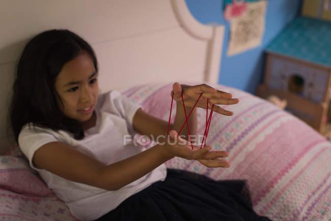 Девочка играет в кошки колыбель игра в спальне дома — стоковое фото