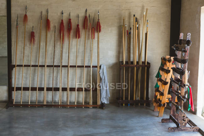Long poles and kung fu spears arranged on racks in martial arts studio. — Stock Photo