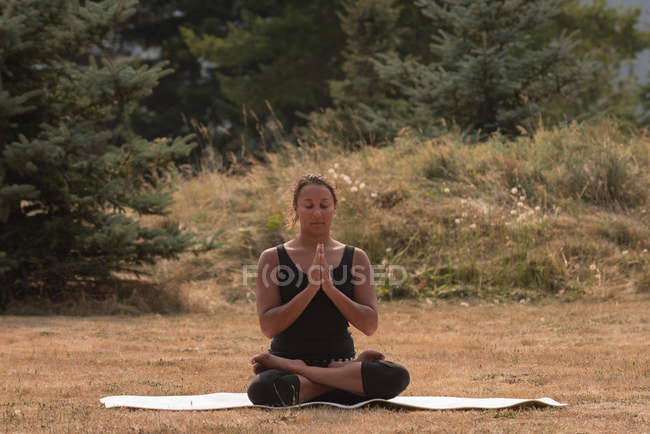 Fit woman sitting in meditating posture on an open ground an a sunny day — Stock Photo