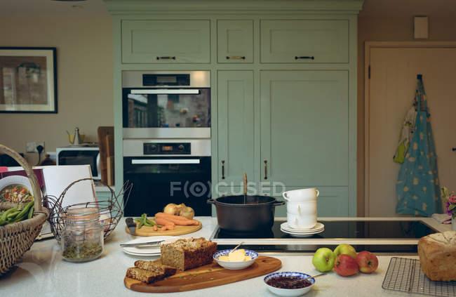 Vario alimento gustoso sul tavolo in cucina accogliente — Foto stock