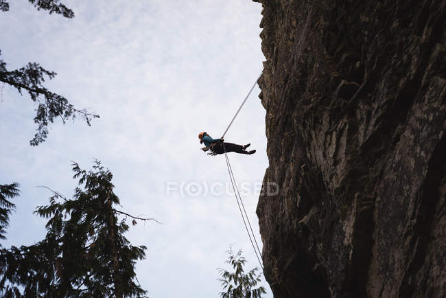 Низкий угол обзора скалолаза, поднимающегося по скалистой скале — стоковое фото