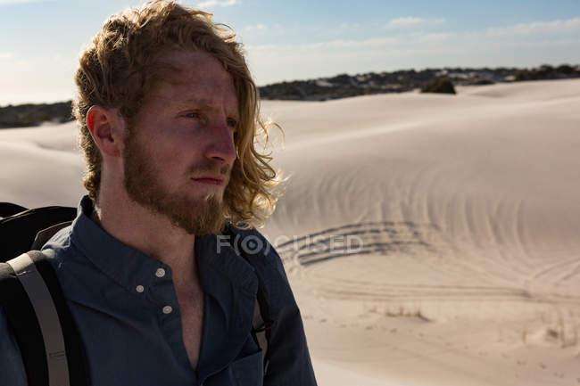 Мужчина-турист с рюкзаком стоит на песке в солнечный день — стоковое фото