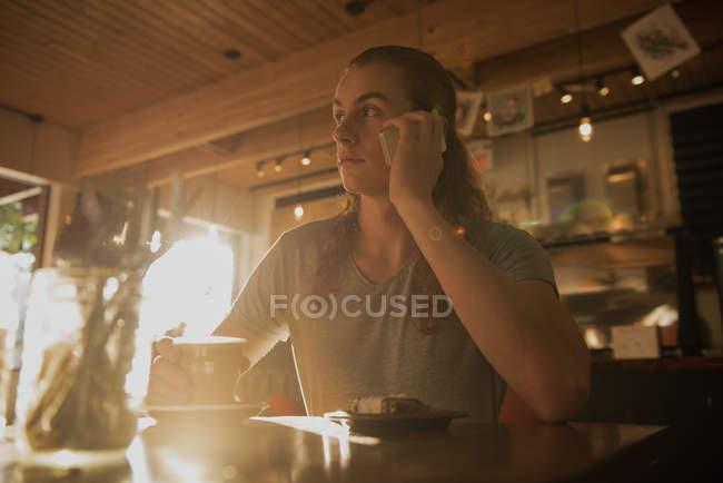 Человек, говорят на мобильном телефоне имея кофе в кафе — стоковое фото