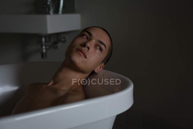Jovem atencioso relaxando na banheira no banheiro — Fotografia de Stock