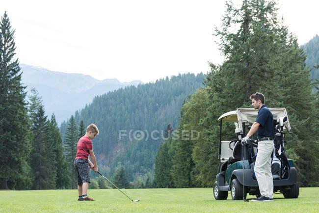 Pai ajudando seu filho a jogar golfe no campo — Fotografia de Stock