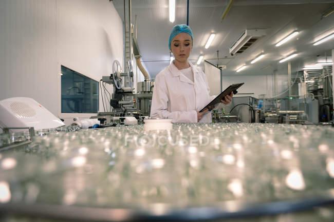 Жіночий працівник моніторингу скляні банки з конвеєра на заводі — стокове фото