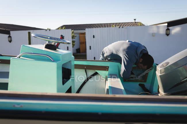 Человек проверяет моторную лодку на заднем дворе . — стоковое фото