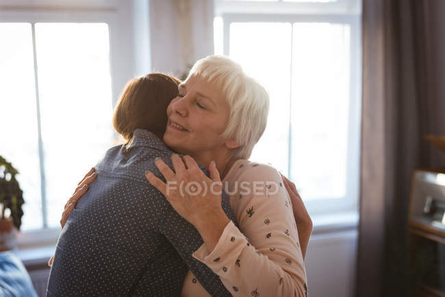 Donna anziana e figlia che si abbracciano in salotto a casa — Foto stock