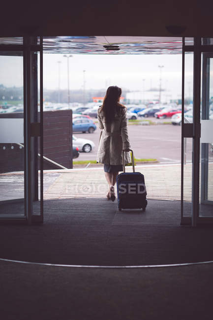 Rear view of businesswoman walking out of the hotel room with baggage — Stock Photo