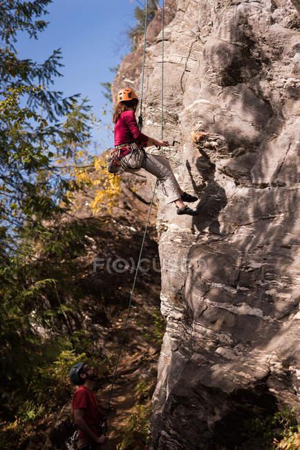 Femme grimpeuse luttant sur la montagne rocheuse par une journée ensoleillée — Photo de stock