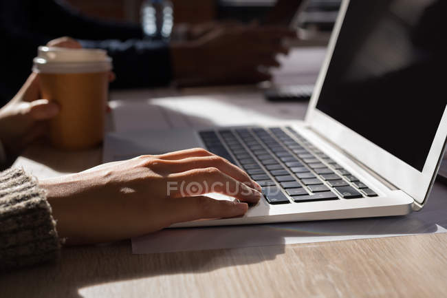 Business colleagues working on laptop at office — Stock Photo