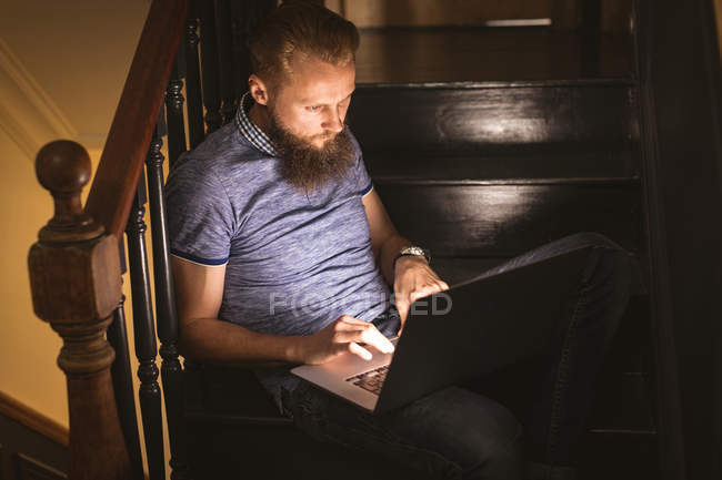 Close-up of man using his laptop while sitting on staircase at home — Stock Photo