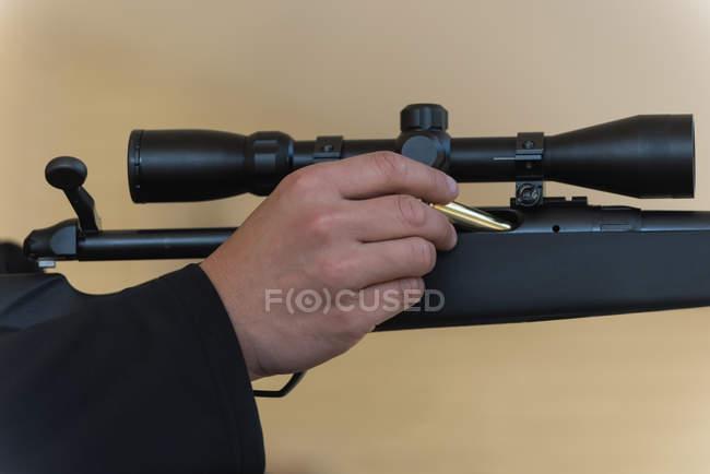 Крупный план человека, загружающего пулю в снайперскую винтовку — стоковое фото