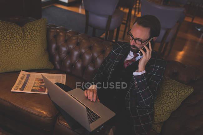 Geschäftsmann greift zum Handy, während er Laptop in Bar benutzt — Stockfoto