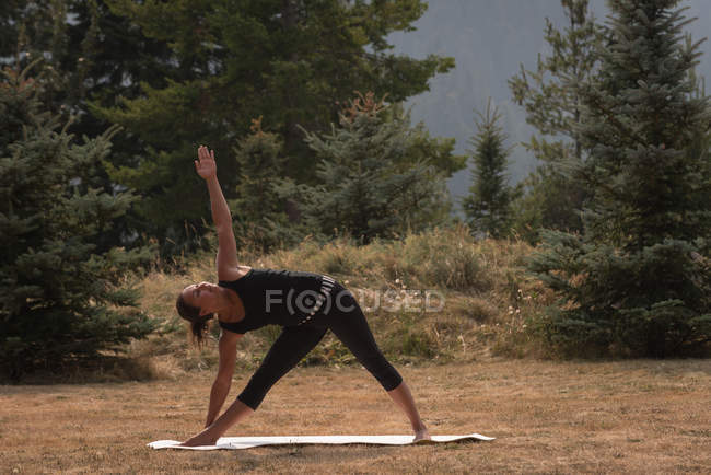 Fit woman performing stretching exercise on an open ground on a sunny day — Stock Photo