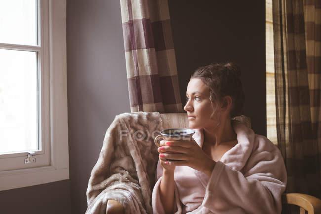 Donna premurosa che prende un caffè in camera da letto e guarda attraverso la finestra a casa . — Foto stock