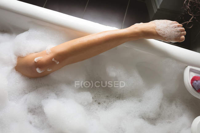 Cropped view of leg of woman taking bath with foam in bathtub at home. — Stock Photo
