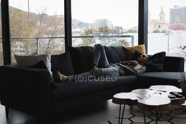 Young man sleeping in living room at home — Stock Photo