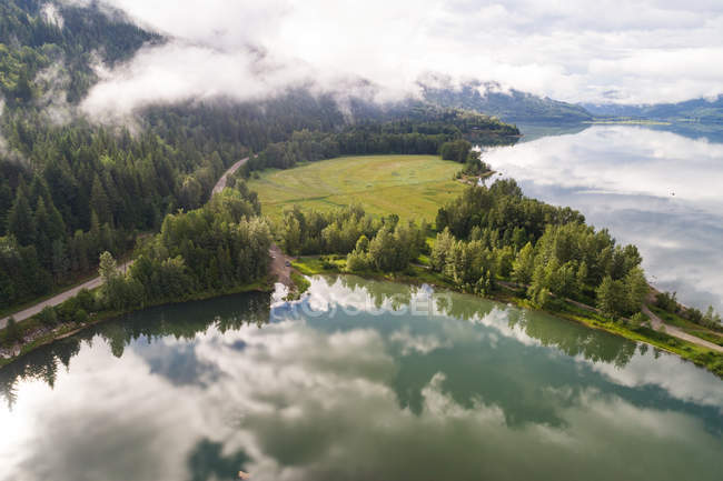 Clouds reflecting in the river near the forest landscape — Stock Photo