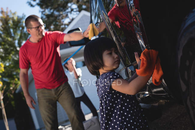 Father and daughter washing car with sponge and duster outside garage — Stock Photo
