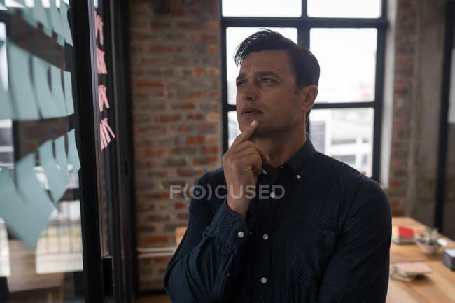 Продуманий бізнесмен, дивлячись на наліпок в офісі. — стокове фото
