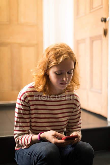 Крупный план женщины, сидящей на лестнице с помощью мобильного телефона — стоковое фото