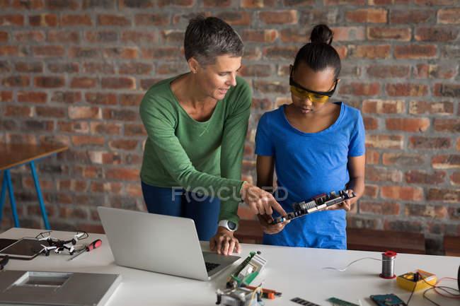 Mère expliquant fille sur circuit imprimé dans le bureau . — Photo de stock