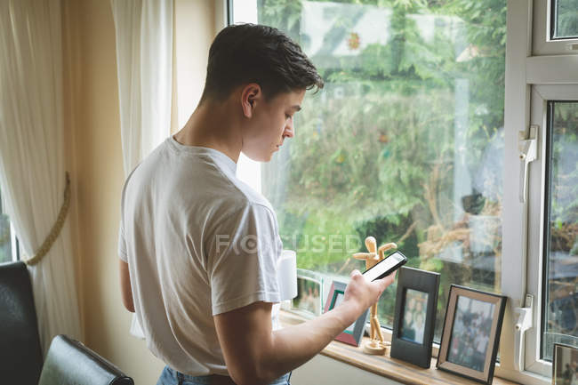 Человек, использующий мобильный телефон за окном дома . — стоковое фото