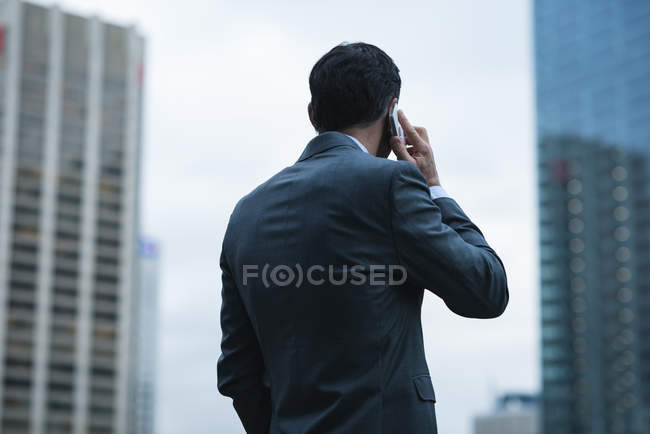 Rear view of businessman talking on mobile phone against sky scrapers — Stock Photo