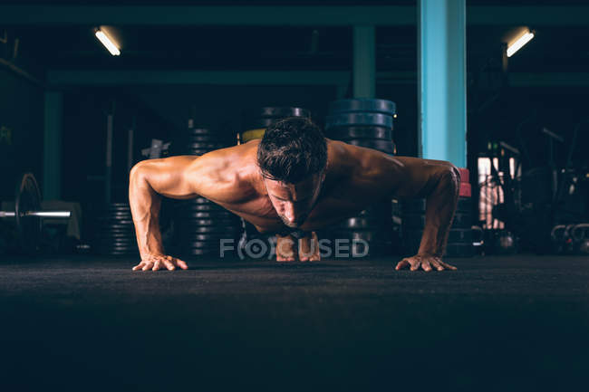 Determined muscular man doing push-up in fitness studio — Stock Photo