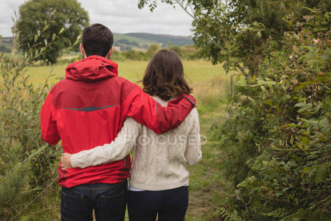 Affectionate standing with arm around near countryside — Stock Photo