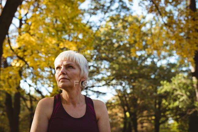 Mujer senior pensativa en un parque en un día soleado - foto de stock