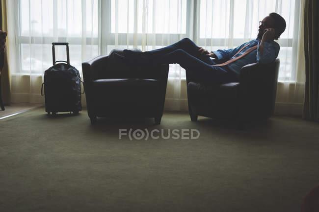 Geschäftsmann telefoniert mit Handy, während er sich im Hotelzimmer auf Sessel lehnt — Stockfoto