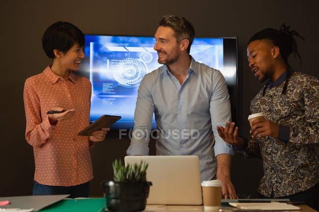 Усміхаючись керівників обговорювати над ноутбук в конференц-залі, в офісі. — стокове фото